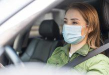 Mulher dirigindo o seu carro usando máscara de proteção