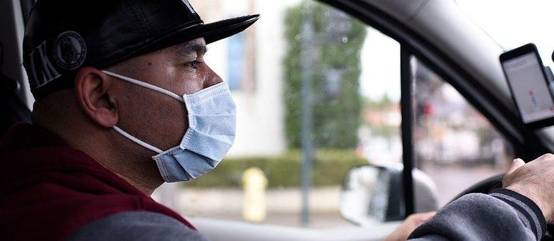 Homem dirigindo e usando máscara de proteção.